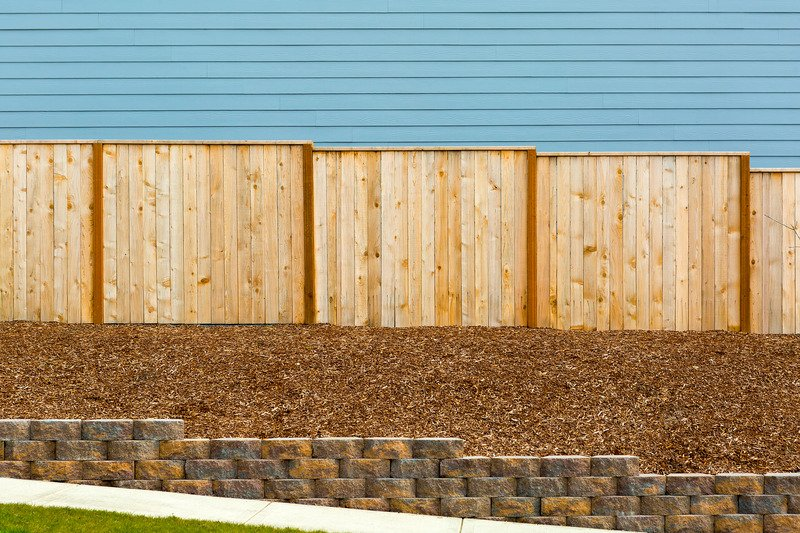 Brick retaining walls on the side of a house, with bark - Mornington